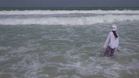 Adolescente en la ropa alegre que salta en las ondas del Golfo Pérsico en la playa del vídeo de la cantidad de la acción de Dubai metrajes