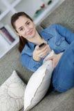 Adolescente en la sala de estar del apartamento en la televisión de observación sofal Imagen de archivo libre de regalías