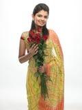 Adolescente en la sari que sostiene rosas rojas Fotografía de archivo