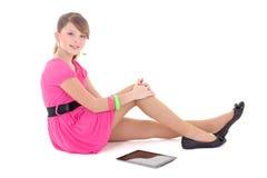 Adolescente en la sentada rosada con PC de la tablilla Imagen de archivo