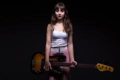 Adolescente en la sombra que sostiene la guitarra Imagen de archivo libre de regalías