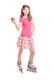 Adolescente en las cuchillas del rodillo que sostienen una manzana Imágenes de archivo libres de regalías