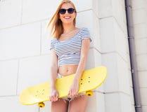 Adolescente en las gafas de sol que sostienen el monopatín Imagen de archivo libre de regalías