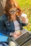 Adolescente en lentes con el ordenador portátil y el café Foto de archivo libre de regalías