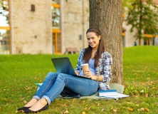 Adolescente en lentes con el ordenador portátil y el café Imagenes de archivo