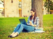 Adolescente en lentes con el ordenador portátil y el café Fotos de archivo