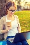 Adolescente en lentes con el ordenador portátil y el café Foto de archivo