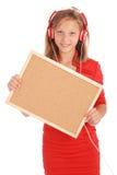 Adolescente en los auriculares, llevando a cabo el tablero del corcho Imagenes de archivo
