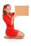 Adolescente en los auriculares, llevando a cabo el tablero del corcho Imágenes de archivo libres de regalías
