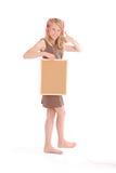 Adolescente en los auriculares, llevando a cabo el tablero del corcho Imagen de archivo libre de regalías