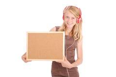Adolescente en los auriculares, llevando a cabo el tablero del corcho Imagen de archivo