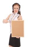 Adolescente en los auriculares, llevando a cabo el tablero del corcho Fotos de archivo libres de regalías
