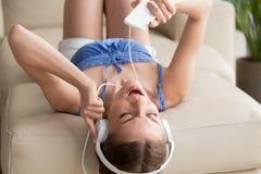 Adolescente en los auriculares que mienten en el sofá, disfrutando de música en el teléfono Fotografía de archivo libre de regalías