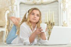 Adolescente en los auriculares que mienten en piso Imagen de archivo libre de regalías