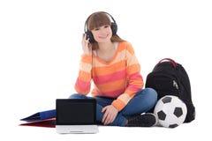 Adolescente en los auriculares que se sientan con el ordenador portátil Foto de archivo