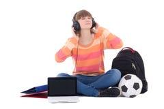 Adolescente en los auriculares que se sientan con el ordenador portátil aislado en blanco Foto de archivo libre de regalías