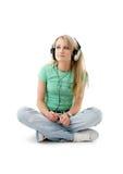 Adolescente en los auriculares que se sientan en el piso Imágenes de archivo libres de regalías