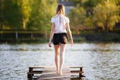 Adolescente en los pantalones cortos negros que se colocan en el embarcadero Imagen de archivo