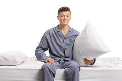 Adolescente en los pijamas que se sientan en una cama y que sostienen una almohada Fotografía de archivo libre de regalías