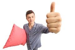 Adolescente en los pijamas que sostienen una almohada y que hacen un pulgar encima de la GE Imagen de archivo