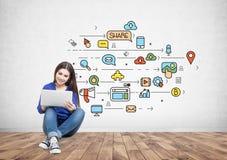 Adolescente en los vaqueros con un ordenador portátil, medio social Imagen de archivo libre de regalías