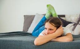Adolescente en los vaqueros que ponen en su cama Fotografía de archivo libre de regalías