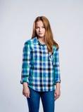 Adolescente en los vaqueros y la camisa comprobada, tiro del estudio Imagen de archivo