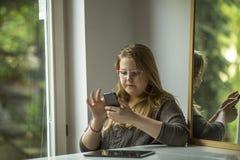Adolescente en los vidrios con smartphone Fotos de archivo