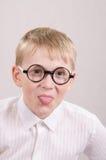 Adolescente en los vidrios que muestran la lengua Fotografía de archivo