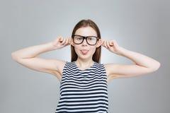 Adolescente en los vidrios que muestran la lengua y que hacen la cara divertida Fotografía de archivo libre de regalías
