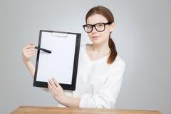 Adolescente en los vidrios que muestran y que señalan en el tablero en blanco Foto de archivo libre de regalías