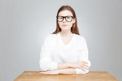 Adolescente en los vidrios que se sientan derecho en la tabla Imagenes de archivo