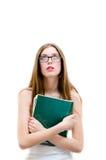 Adolescente en los vidrios que sostienen el libro y que miran para arriba en el fondo blanco del copyspace Fotografía de archivo