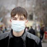 Adolescente en máscara de la gripe Imagenes de archivo