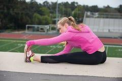 Adolescente en músculos que activan de la chaqueta rosada sobre campo Fotos de archivo