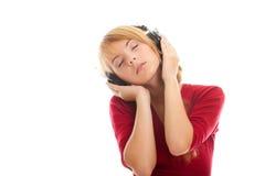 Adolescente en música que escucha de la blusa roja brillante Imagenes de archivo