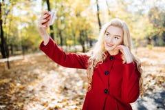 Adolescente en otoño en el parque que toma un selfie en el teléfono elegante Mujer joven feliz hermosa que toma una foto de sí mi Foto de archivo libre de regalías