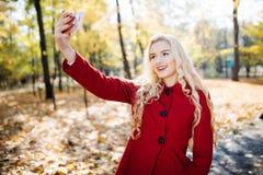Adolescente en otoño en el parque que toma un selfie en el teléfono elegante Mujer joven feliz hermosa que toma una foto de sí mi Imagen de archivo