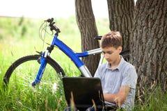 Adolescente en parque con la nueva computadora portátil Fotos de archivo