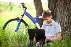 Adolescente en parque con la nueva computadora portátil Imágenes de archivo libres de regalías