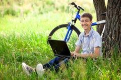 Adolescente en parque con la nueva computadora portátil Fotografía de archivo