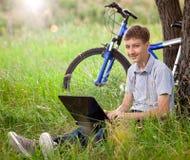Adolescente en parque con la nueva computadora portátil Foto de archivo