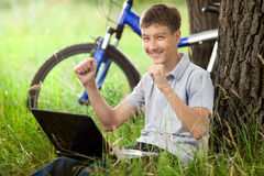 Adolescente en parque con la nueva computadora portátil Fotos de archivo libres de regalías