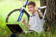 Adolescente en parque con la nueva computadora portátil Fotografía de archivo libre de regalías