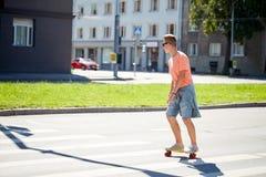 Adolescente en paso de peatones de la ciudad de la travesía del monopatín Imagen de archivo libre de regalías