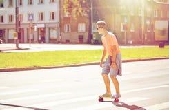 Adolescente en paso de peatones de la ciudad de la travesía del monopatín Fotografía de archivo libre de regalías