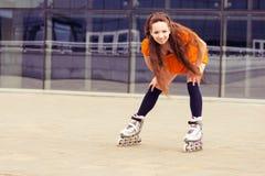 Adolescente en pcteres de ruedas en el edificio moderno del fondo Imagen de archivo libre de regalías