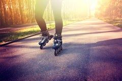 Adolescente en pcteres de ruedas en el verano Imagen de archivo