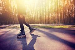 Adolescente en pcteres de ruedas en el verano Fotografía de archivo