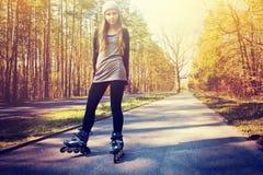 Adolescente en pcteres de ruedas en el verano Foto de archivo libre de regalías